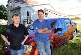 John Patrick and Sharon Barrie lean on Patrick's Chrysler Avenger parked outside Barrie's apartment in Dominion. Patrick, who was homeless, had lived in his car behind a store in Sydney for four months and was unable to turn it on for heat after losing the key a month ago. Sharon Montgomery-Dupe/Cape Breton Post