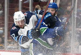 Canucks' Kyle Burroughs is checked into the boards by Winnipeg Jets' Jansen Harkins during NHL pre-season action in Vancouver on Oct. 3.