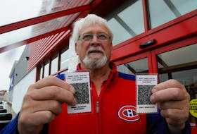 Mount Pearl resident Ray Pardy, a retired Newfoundland Power lineman, displays his and his wife Marie's laminated QR codes Wednesday afternoon, Oct. 30. Joe Gibbons • The Telegram