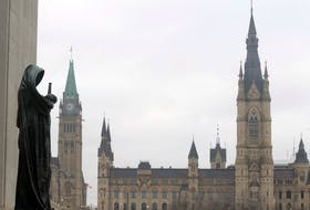 A statue representing justice looks out from the Supreme Court of Canada over the Parliamentary precinct in Ottawa. There is a strong feeling, even among MPs who are vaccinated, that mandatory vaccination is an infringement on freedom of movement and the constitutional rights of Canadians.