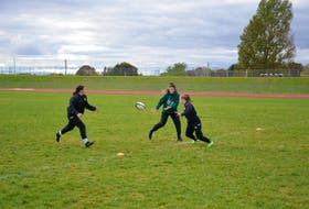 Sophie Carragher, centre, passes the ball to Brinten Comeau, left, while Maddison Clements defends during a drill at the UPEI women's rugby team practice on Oct. 19. Earlier in the day, the Panthers were ranked in the USPORTS top-10 rankings for the first time in the history of the program.