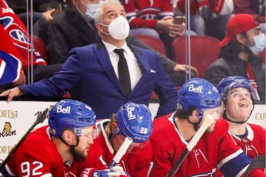 Canadiens head coach Dominique Ducharme checks the clock while standing behind Jonathan Drouin, from left, Christian Dvorak, Josh Anderson and Cole Caufield Tuesday night 5-0 loss to the Sharks at the Bell Centre.