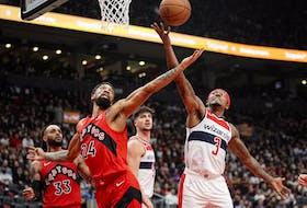 Toronto Raptors centre Khem Birch and Washington Wizards guard Bradley Beal go after a rebound.