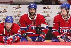 Montreal Canadiens' Jonathan Drouin, Mathieu Perreault and Josh Anderson stay on the bench following the final siren in their loss to the Carolina Hurricanes in Montreal on Oct. 21, 2021.