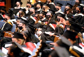 Masked graduates watch the first convocation ceremony for the university since the fall of 2019.