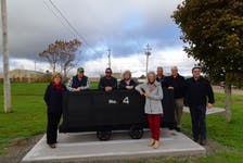 (From left) Cumberland municipal councillor Rod Gilroy, Heather Henwood, Coun. Angel McCormick, Ann Stone, Jamie Henwood, Mayor Murray Scott, Coun. Mark Joseph and Charlie Martin of Martin's Metal Works stand beside one of two original coal cars refurbished as a memorial to Springhill's coal mining heritage.