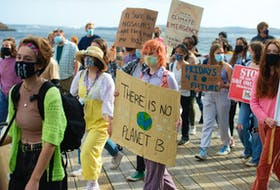 Students march along the Halifax waterfront as part of a global Climate Strike rally on Friday, Oct. 22, 2021.