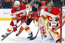 Calgary Flames defencemen Erik Gudbranson battles with Edmonton Oilers forward Zach Hyman in front of Flames goaltender Jacob Markstrom during a pre-season game at Rogers Place in Edmonton on Oct. 4, 2021.