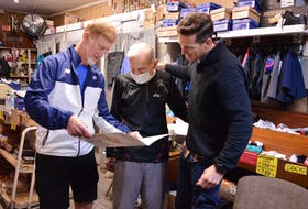 P.E.I. runners Francis Fagan, left, and Stan Chaisson, right, hand an 80th birthday card to long-time runner and sneaker salesman Salam Hashem on Oct. 22.