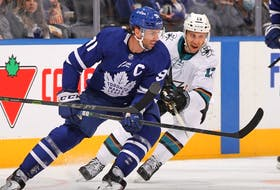Nick Bonino of the San Jose Sharks skates against John Tavares of the Toronto Maple Leafs during an NHL game at Scotiabank Arena on October 22, 2021 in Toronto, Ontario, Canada.