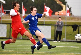 Nolan Brophy of the Sydney Academy Wildcats, right, takes a shot on goal as he's chased by Jack Gogan of the Riverview Ravens during School Sport Nova Scotia Highland Region Division 1 soccer championship action at Open Hearth Park in Sydney, Friday. Sydney Academy won the game 1-0. JEREMY FRASER/CAPE BRETON POST