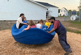 Katie Devine, with children Parker and Penny, as well Avery and Audrey Johnson (backs to picture), enjoying the inclusive spinner, being spun by Kyle Slack. The installation of the equipment is part of the Debert Elementary School Parent Teacher Association (PTA) Playground Initiative. Devine and Slack are PTA members.