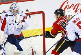 The Calgary Flames' Andrew Mangiapane battles Washington Capitals goaltender Braden Holtby at the Scotiabank Saddledome in Calgary on Oct. 22, 2019.