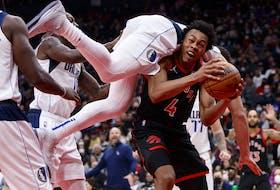 Dwight Powell #7 of the Dallas Mavericks falls over Scottie Barnes on Saturday night.