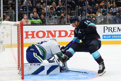 Canucks goalie Thatcher Demko makes the save against Nathan Bastian of the Seattle Kraken in the second period during the Kraken's inaugural home game on Oct. 23, 2021, at Climate Pledge Arena