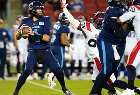 Toronto Argonauts quarterback McLeod Bethel-Thompson (4) looks to pass as he is pressured by Montreal Alouettes defensive lineman Antonio Simmons (93) at BMO Field in Toronto on Sept. 24, 2021.