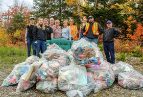Some of the volunteers of the Leigh-Anne Legacy Adopt-a-Highway group stand around a couch they found illegally dumped near the highway and one truck bed worth of full trash bags. The group filled multiple truck beds with trash found at the side of Leigh-Anne's 3.2-kilometre stretch of Port Morien Highway. JESSICA SMITH/CAPE BRETON POST