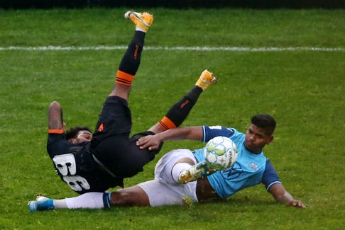 HFX Wanderers' Eriks Santos makes a deft sliding tackle on a sprawling Omar Browne of Forge FC during the second half of their Canadian Premier League match Saturday afternoon at the Wanderers Grounds. - TIM KROCHAK / THE CHRONICLE HERALD