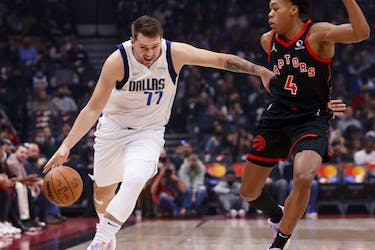 Luka Doncic #77 of the Dallas Mavericks drives against Scottie Barnes #4 of the Toronto Raptors during their NBA game at Scotiabank Arena.