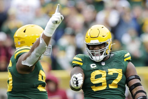 Kenny Clark #97 celebrates with teammates after recording a sack in the fourth quarter against the Washington Football Team in the game at Lambeau Field on October 24, 2021 in Green Bay, Wisconsin.