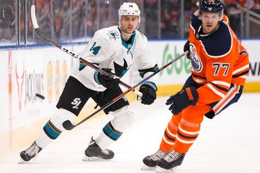 Edmonton Oilers' Oscar Klefbom (77) and San Jose Sharks' Dylan Gambrell (14) watch a flying puck during the second period of a NHL game at Rogers Place in Edmonton, on Saturday, Feb. 9, 2019.