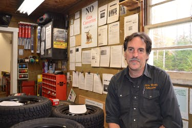 Colin Hawks sits in his automotive garage on Brentwood Road in Colchester County on Monday, Oct. 25, 2021, with clippings and notices about the proposed Alton Gas project dominating the bulletin board behind him.