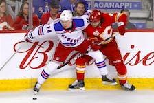 The Calgary Flames' Rasmus Andersson battles the New York Rangers' Kaapo Kakko at the Scotiabank Saddledome in Calgary on Jan. 2, 2020.