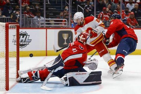 The Calgary Flames' Elias Lindholm scores a goal on Washington Capitals goaltender Vitek Vanecek at Capital One Arena in Washington on Saturday, Oct. 23, 2021.