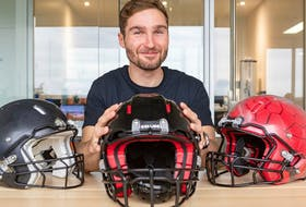 Franck Le Navéaux with a final prototype of a Kollide football helmet, flanked by earlier versions. He is the research coordinator of the Kollide consortium of four Montreal companies which designed the helmet.