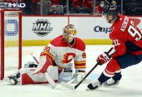 Calgary Flames goaltender Dan Vladar and Washington Capitals centre Evgeny Kuznetsov watch the puck at Capital One Arena in Washington on Saturday, Oct. 23, 2021.