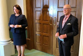 Finance Minister Siobhan Coady and Health Minister Dr. John Haggie speak to reporters outside the House of Assembly chambers Tuesday.