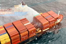 A tugboat pours water on the container ship Zim Kingston after it caught fire off the coast of British Columbia on Oct. 25. Canadian Coast Guard/Handout via REUTERS