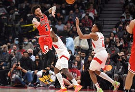 Chicago Bulls guard Lonzo Ball passes the ball away from Toronto Raptors forward Scottie Barnes in the first half at Toronto's Scotiabank Arena on Oct. 25, 2021.