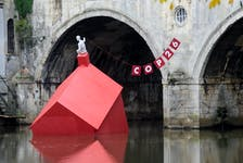 An installation of a 'sinking house' is partly submerged in Bath, Britain on Tuesday to highlight climate change ahead of the COP26 conference. REUTERS/Rebecca Naden