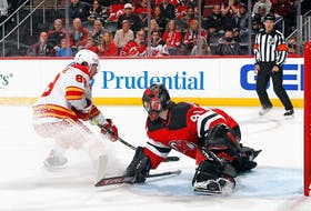 Flames forward Andrew Mangiapane scores his second goal of the game at 12:56 of the first period against Devils goalie Scott Wedgewood at the Prudential Center on Tuesday night in Newark, N.J.