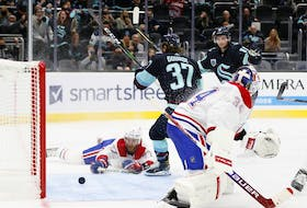 Kraken's Yanni Gourde beats Canadiens goalie Jake Allen as defenceman Brett Kulak can only watch from the ice during the second period in Seattle Tuesday night.