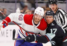 Montreal Canadiens' Joel Armia and Jaden Schwartz of the Seattle Kraken battle for a loose puck during the first period in Seattle Oct. 26, 2021.