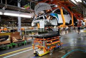 An automated guided vehicle carrying a battery pack moves under a partially assembled 2018 Chevrolet Bolt EV vehicle on the assembly line at General Motors Orion Assembly in Lake Orion, Mich. in 2018.