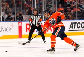 Edmonton Oilers' Evan Bouchard (75) fires a slapshot on Vancouver Canucks' Jaroslav Halak (41) during the third period of preseason NHL action at Rogers Place in Edmonton, on Thursday, Oct. 7, 2021.