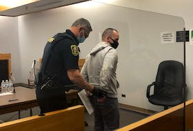 A sheriff handcuffs Bobby Newell and escorts him from a provincial courtroom in St. John's Wednesday morning, Oct. 27.