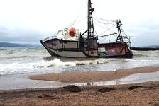 The fishing vessel Northern Tip on its side aground in Iona late afternoon Wednesday, after breaking from the wharf earlier in the day. The Canadian Coast Guard is on site and working with the owner on a recovery plan. Contributed/Jim MacNeil