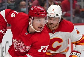 Red Wings left wing Adam Erne looks to pass with Calgary Flames defenceman Rasmus Andersson in hot pursuit during last Thursday's date in Detroit.