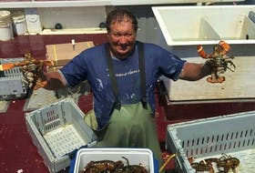 Michael Dominie, a 48-year-old lobster fisherman from Glace Bay, N.S. holds up lobster on the boat he works on. Several years ago, Dominie and his crew survived a hurricane.