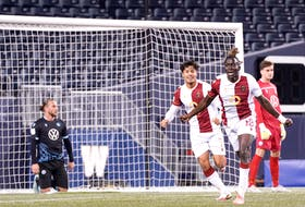 Valour FC's William Akio celebrates his first-half goal while a dejected Peter Schaale and Kieran Baskett of the HFX Wanderers look on during a Canadian Premier League match Tuesday in Winnipeg. - CANADIAN PREMIER LEAGUE