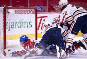 Montreal Canadiens' Brendan Gallagher crashes into the net after diving past Edmonton Oilers goaltender Mikko Koskinen to score in Montreal on March 30, 2021.