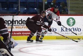 Acadia Axemen forward Cole Rafuse, right, fires a pass across the ice while being defended by Saint Mary's Huskies blue-liner Walter Flower Oct. 27 at the Andrew H. McCain Arena in Wolfville.