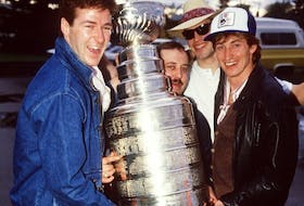 Edmonton Oilers Kevin Lowe, left, equipment manager Lyle 'Sparky' Kulchisky, Mark Messier and Wayne Gretzky hold the Stanley Cup after leaving David's Restaurant in Edmonton on May 21, 1984.