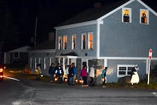 Participants in one of the walking lantern tours of the historic district in Barrington, walk past the Homer house, which has been decked out for Halloween.  KATHY JOHNSON