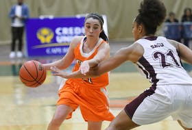 Cape Breton Capers guard MacKenzee Ryan, left, works her way around a defender during Atlantic University Sport women's basketball action at Sullivan Field House in Sydney during the 2019-20 season. The Glace Bay product is expected to be a leader on a young Capers team this season. CONTRIBUTED • VAUGHAN MERCHANT, CBU ATHLETICS
