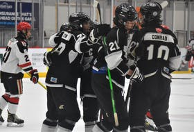 The Bombers celebrate Logan Roop's (#21) second-period, power-play goal versus the Bearcats.
